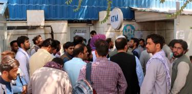 Afganos aguardan este lunes afuera de un banco cerrado en Kabul para intentar retirar dinero (EFE )